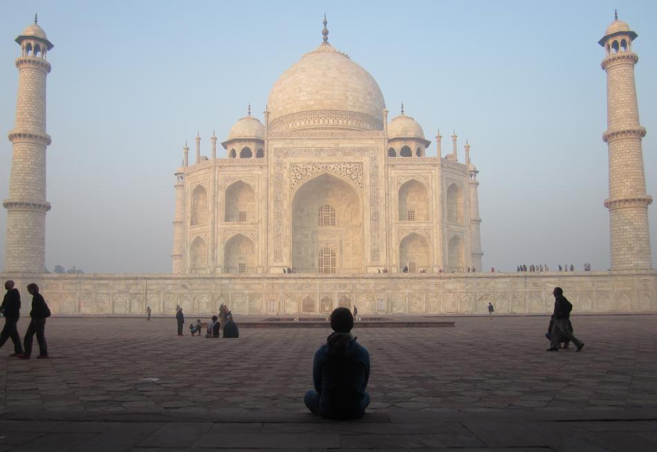 Une silhouette d'un étudiant assis sur le sol faisant face au Taj Mahal en arrière-plan