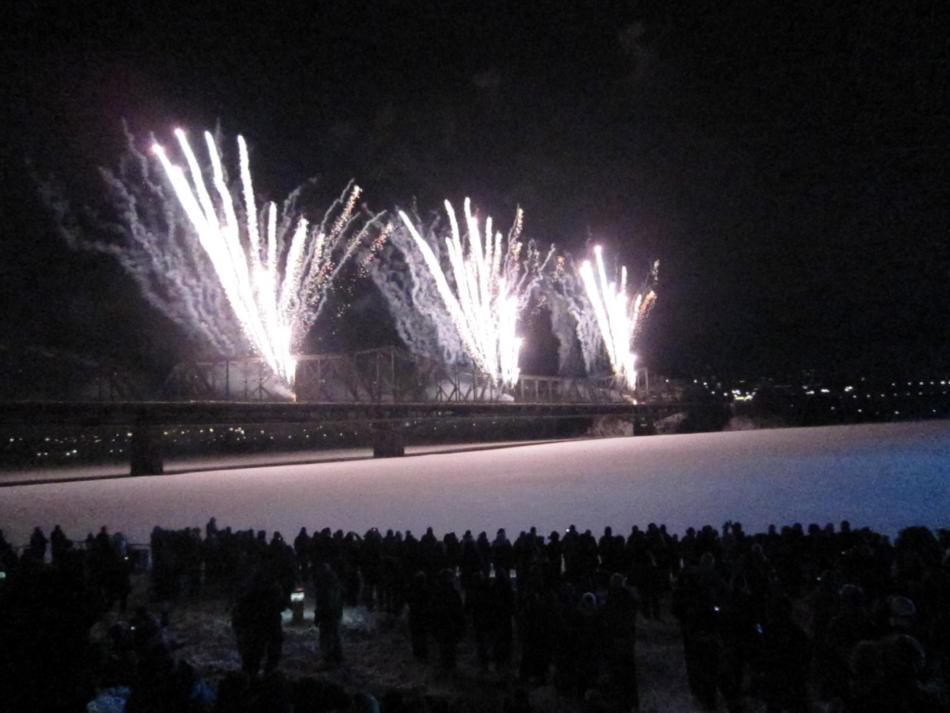 Trois feux d'artifices tirés d'un pont sur une rivière recouverte de neige.