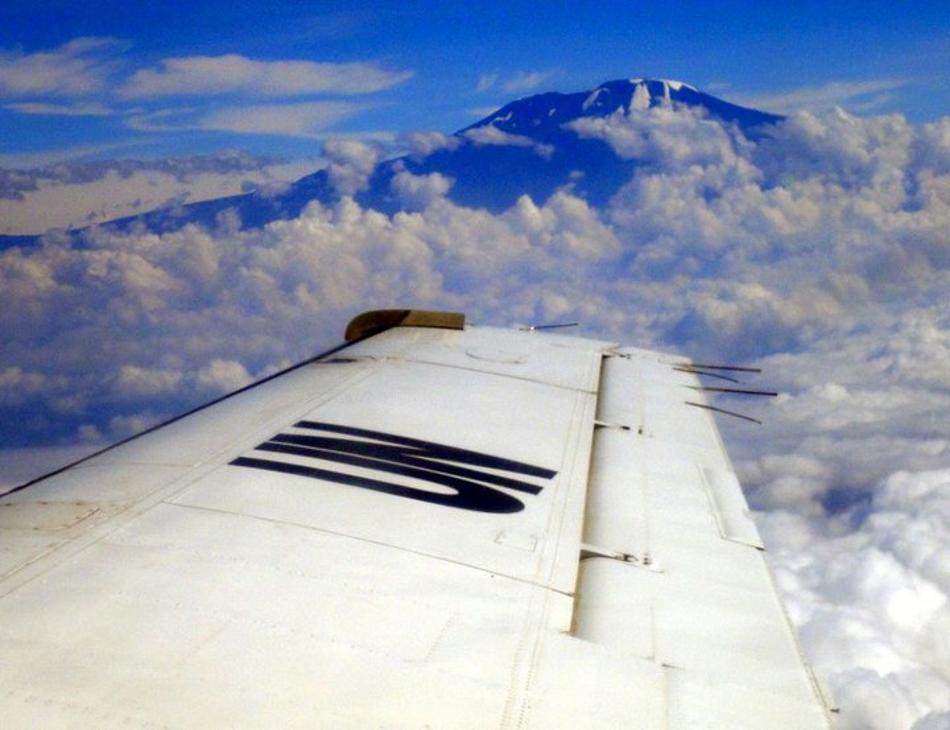 Vue du hublot d'un avion par-dessus son aile sur lequel on voit le logo des Nations Unies. Le haut d'une montagne est visible à l'horizon par-dessus les nuages.