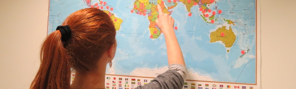 Student pointing a world map