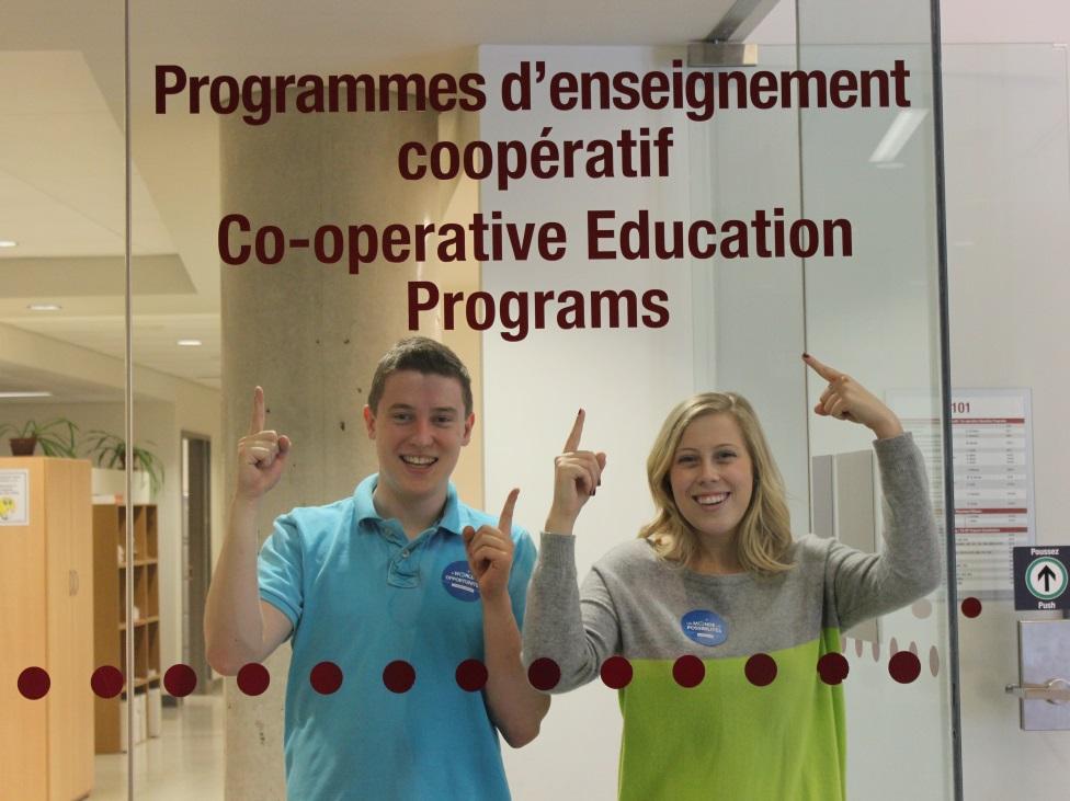Deux étudiants coop pointent l'enseigne du Bureau des Programmes d'enseignement coopératif