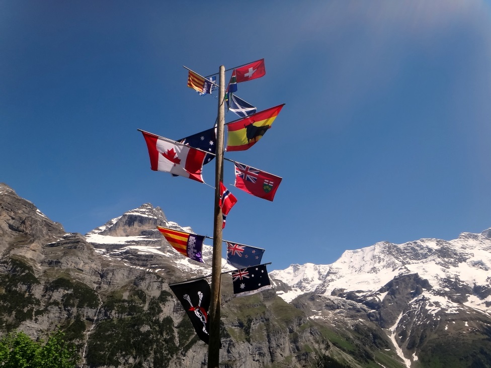 Flags from different countries in the mountains