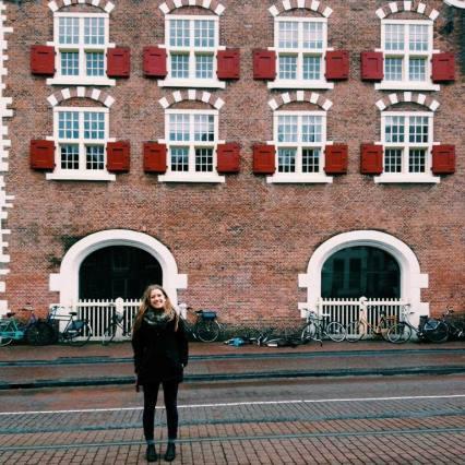 étudiante en face d'une bâtisse à La Hague aux Pays-Bas